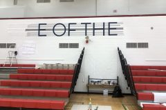 Painting the lettering behind the bleachers